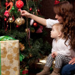 Happy mother decorating christmas tree with her baby — Stock Photo #15658567