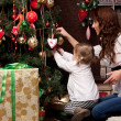 Stock Photo: Happy mother decorating christmas tree with her baby