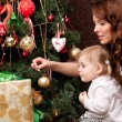 Happy mother decorating christmas tree with her baby — Stock Photo #15658657