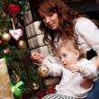 Happy mother decorating christmas tree with her baby — Stock Photo #15658719