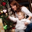 Happy mother decorating christmas tree with her baby — Stock Photo #15658783