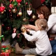 Happy mother decorating christmas tree with her baby — Stock Photo #15658847