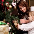 Happy mother decorating christmas tree with her baby — Stock Photo #15658931