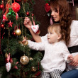 Happy mother decorating christmas tree with her baby — Stock Photo #15659081
