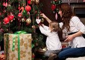 Glückliche mutter dekorieren weihnachtsbaum mit ihrem baby — Stockfoto