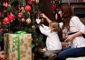 Happy mother decorating christmas tree with her baby — Stok fotoğraf