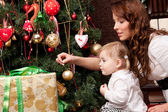 Happy mother decorating christmas tree with her baby — Zdjęcie stockowe
