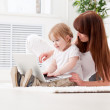 Happy young mother and her daughter using a laptop — Stock Photo