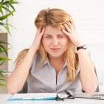 kvinna med huvudvärk sitter vid bordet — Stockfoto