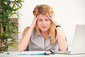 Woman with headache sitting at the table — Stock Photo