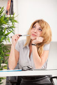 Woman looking up and sitting at the desk — Stock Photo