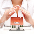 Female hands saving small house with a roof — Stock Photo #31875445