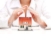 Female hands saving small house with a roof — Stock Photo