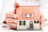 Pisture of man and woman hands holding paper house — Stock Photo