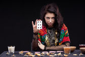 Attractive young fortune teller holdin card — Stockfoto