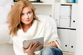 Woman sitting and holding tablet — Stock Photo