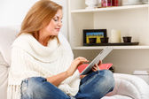 Woman sitting and using tablet — Stock Photo