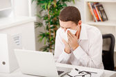 Man sneezing while working — Stock Photo
