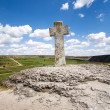 Stone cross under blue sky — Stock Photo