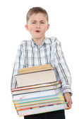The schoolchild with a huge pile of heavy books in hands. — Stock Photo
