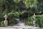 Artistic statues adorn the shady lane — Stock Photo