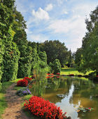 A pond and red flower beds — Stock Photo