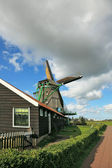 A windmill and a barn on a green hillock — Stock Photo