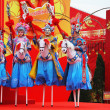 Beautiful dancers on stilts depict riders — Stock Photo #15850019