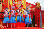 Beautiful dancers on stilts depict riders — Stock Photo