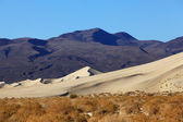 Sand dune in Eureka and red rocks — Stock Photo