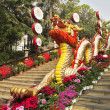 The ladder in the Chinese park - a red dragon and bright flowers - Stock Photo