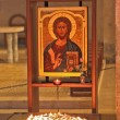Magnificent old icon and a burning candles — Stockfoto