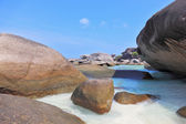 Finest white sand between huge black cliffs — Stock Photo