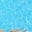 Slender young girl sunning in the pool — Stockfoto