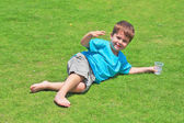 The charming four-year-old boy on a green grassy lawn — Stock Photo