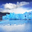 Stock Photo: Grey glacier moves down the water