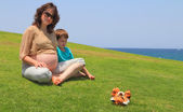 The pregnant woman rests with little son  — Stock Photo
