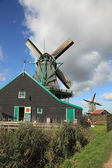 Windmill and barn on a green hill — Stock Photo