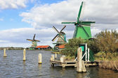 Three windmills and berthing columns on the bank of the channel — Stock Photo