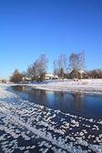 Winter dorp aan kust rivier — Stockfoto