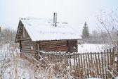 Gammal lantlig trähus bland snö — Stockfoto