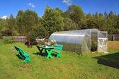 Garden furniture near plastic hothouse — Stock Photo
