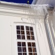 Icicles on roof of white building — Stock Photo #13566372