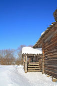 Rural wooden house amongst snow — Stock Photo