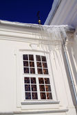 Icicles on roof of the white building — Stock Photo