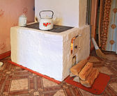 Brick stove in rural wooden house — Stock Photo