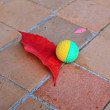 Ball near red sheet on tiled floor — Stock Photo