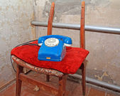 Old telephone on broken chair — Stock Photo