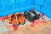 Aging footwear on porch of the rural building — Stock Photo
