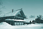 Wooden rural house amongst snow — Stock Photo
